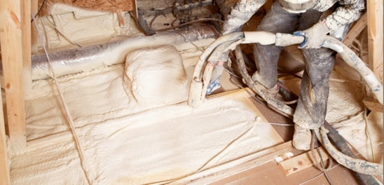 Picture of a contractor filling in a crawlspace is spray foam
