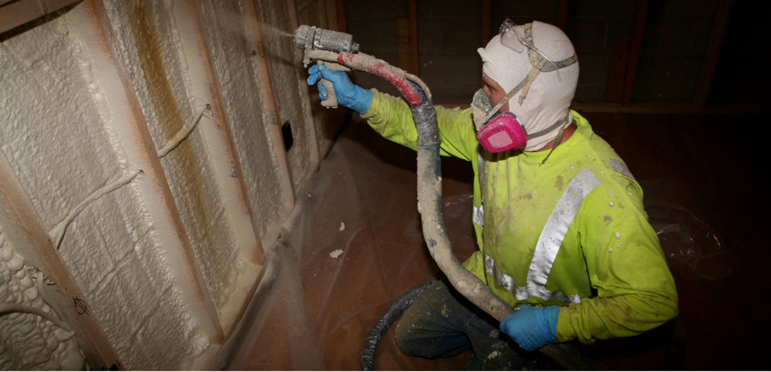 Picture of a contractor spraying foam in a crawlspace